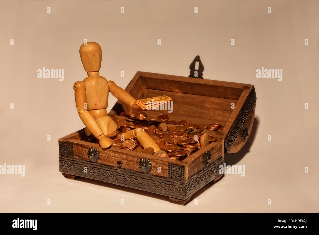Wooden figure sitting in a wooden box with money, bill on the hand - Stock Image