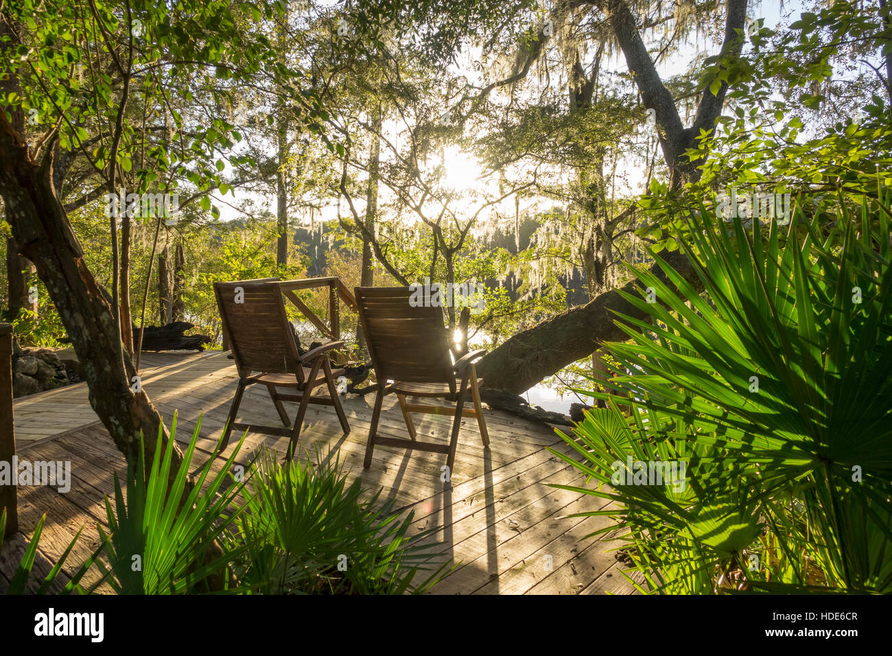Deck chairs overlooking scenic river backlit by afternoon sun - Stock Image