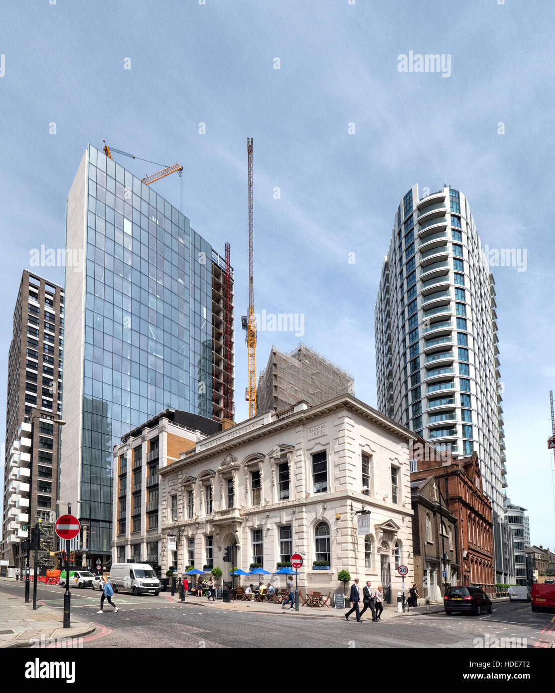 The Eastman Dispensary building dwarfed by towering new buildings in and around Leman Street in Whitechapel East - Stock Image