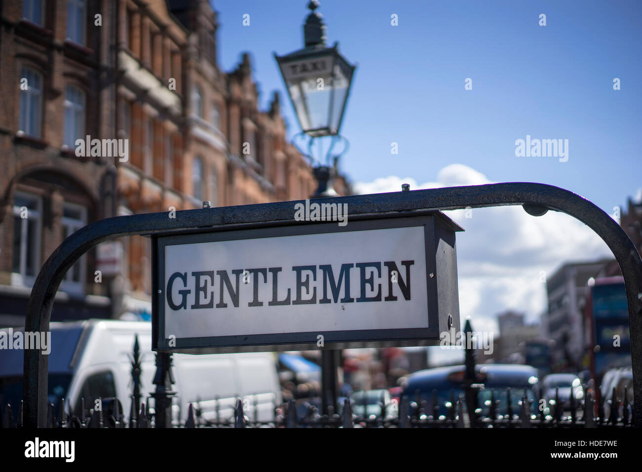 Gentlemen sign over public conveniences, lavatories on Camden Town High Street with a Victorian taxi lampost - Stock Image