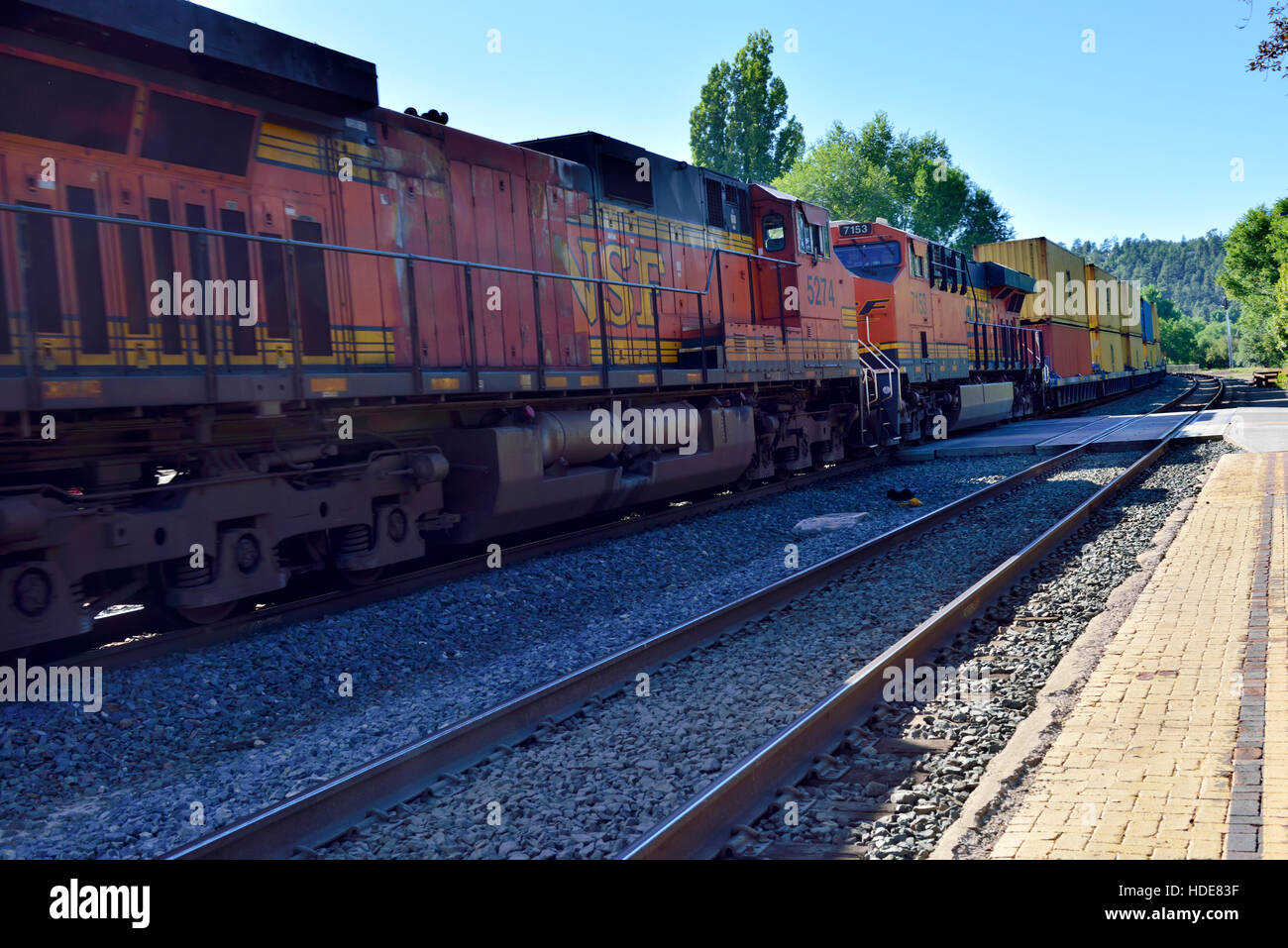 Multiple BNSF diesel locomotives in the middle of long train of shipping containers at Flagstaff, Arizona - Stock Image