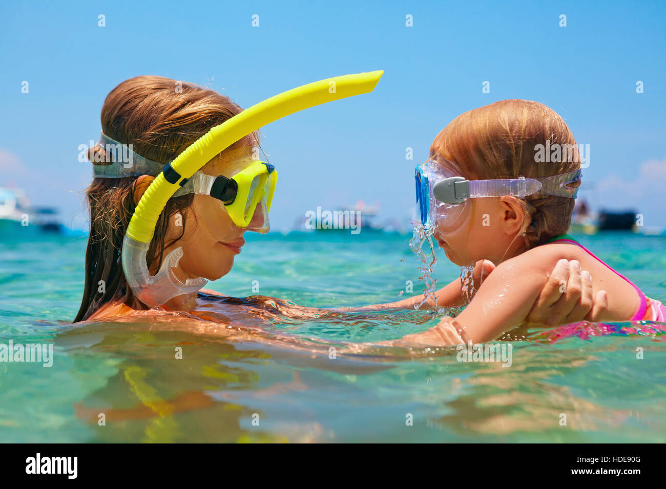 Happy family. Mother with baby girl dive underwater in sea pool. Healthy lifestyle, active parent, water sport outdoor - Stock Image