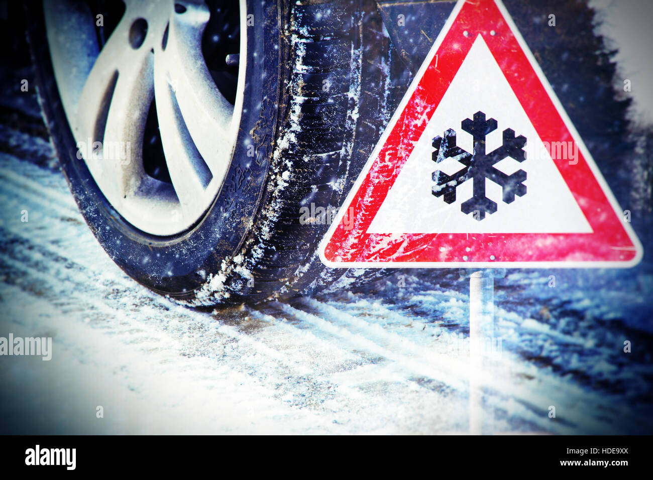 Car tires on winter road with traffic sign Stock Photo