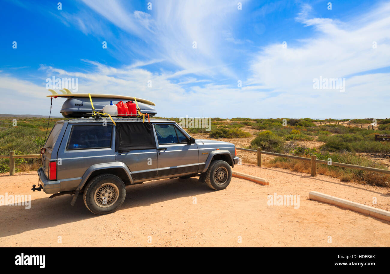 A Jeep Cherokee with a surfboard and bottles of water tied to the roof rack - Stock Image