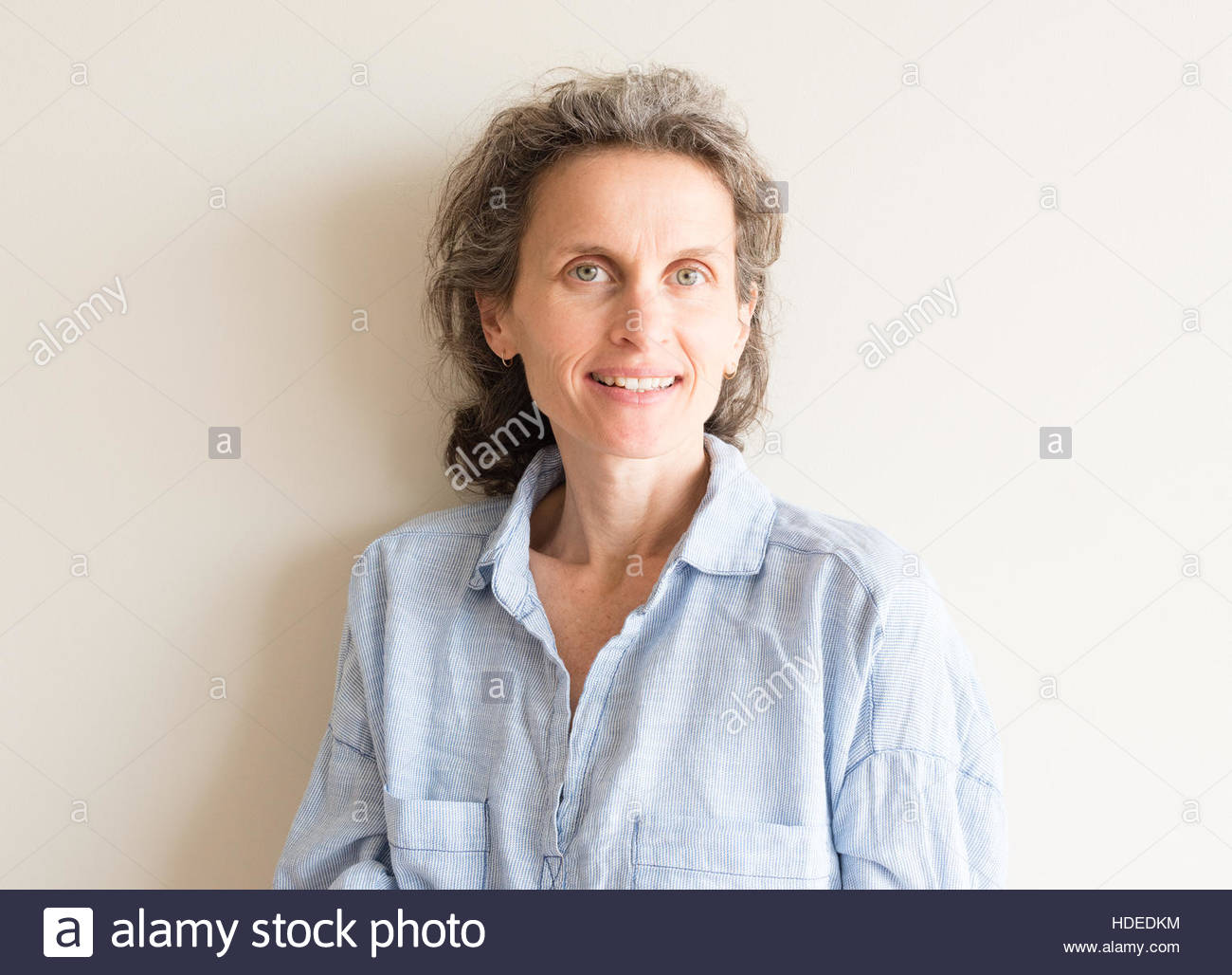 Natural looking middle aged woman with grey hair and blue shirt smiling - Stock Image