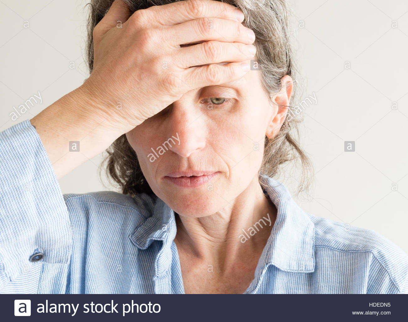 Close up of middle aged woman with hand on forehead covering one eye - Stock Image