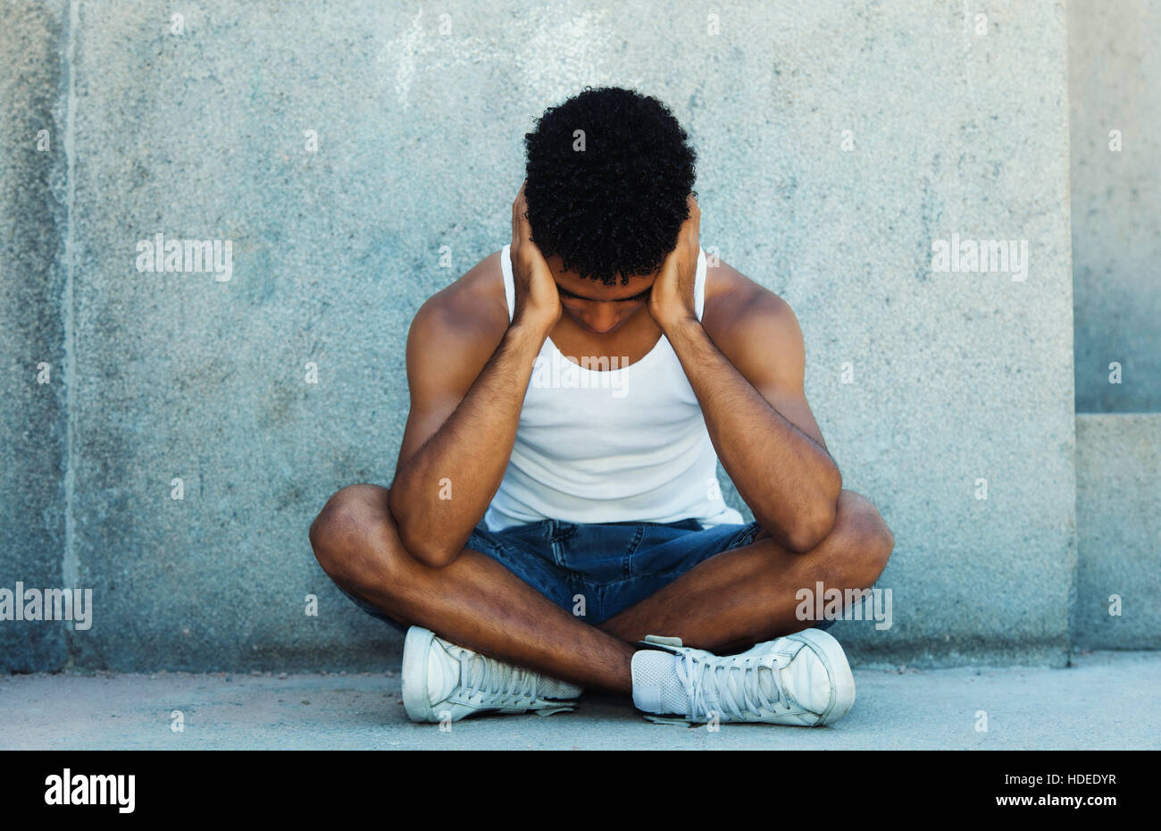 Poor homeless latin young adult thinking about his problems - Stock Image