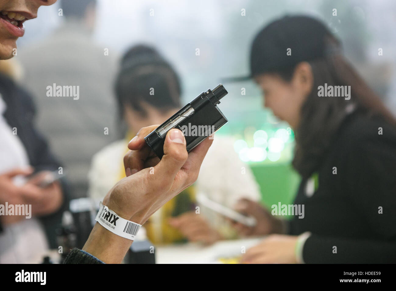 MOSCOW - 9 DECEMBER,2016: International Vape Expo.Man try new vaper ejuice liquid and vapind device gadget - Stock Image