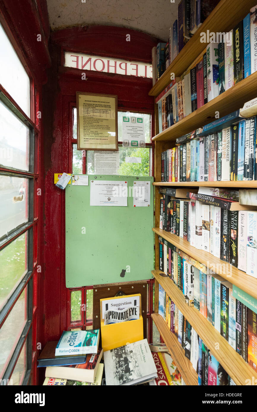 red telephone box uses - village library - Stock Image