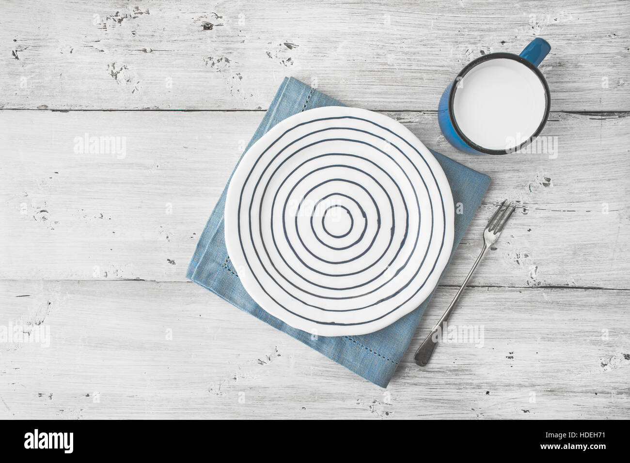 Ceramic plate with fork and cup of milk on the wooden table top view - Stock Image
