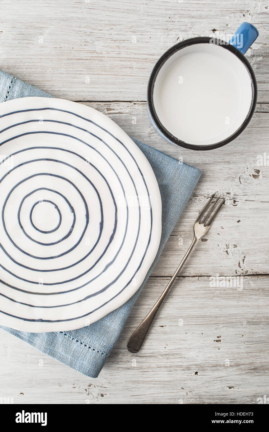 Ceramic plate with fork and cup of milk on the wooden table vertical - Stock Image