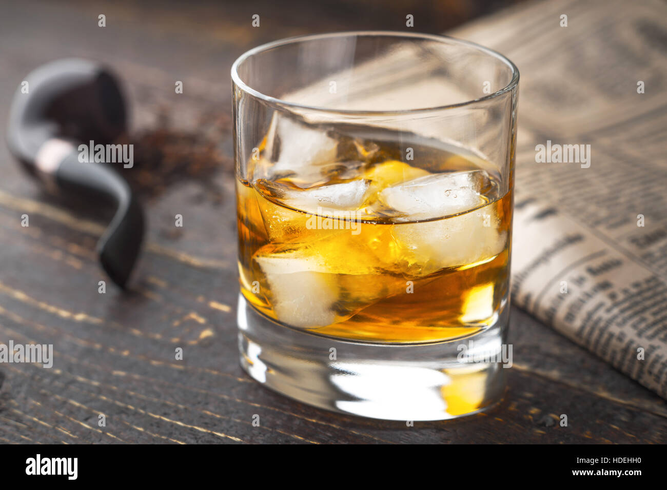 Whiskey with ice  and blurred pipe and newspaper - Stock Image