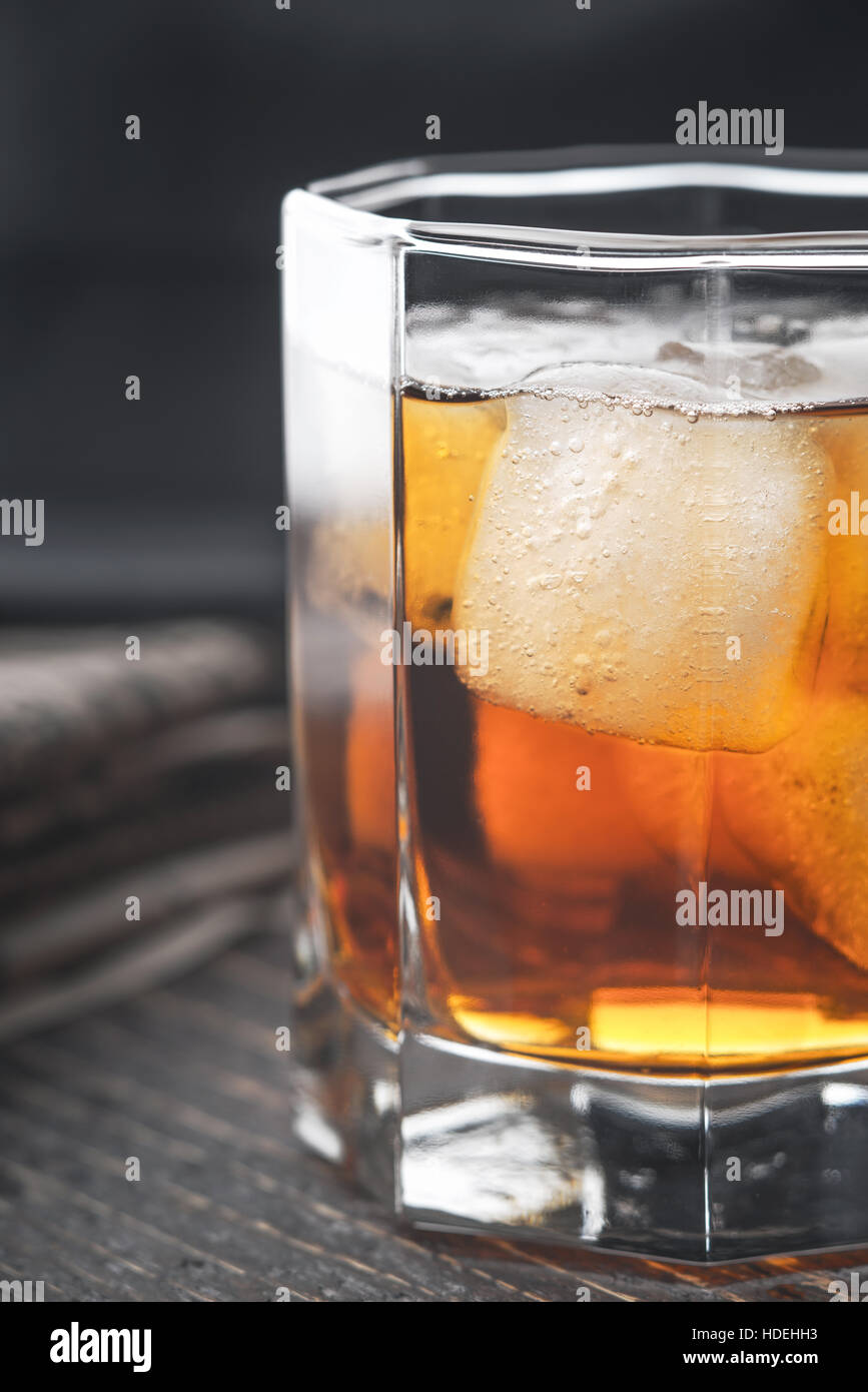 Whiskey with ice on the wooden table vertical - Stock Image