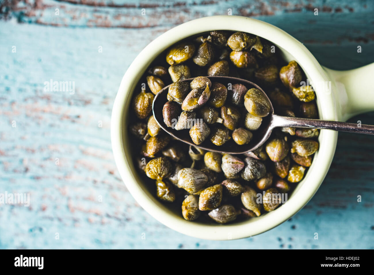 Capers in the bowl on the light blue background top view - Stock Image