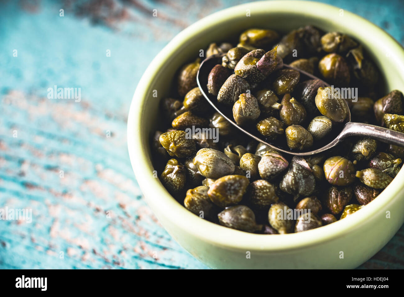 Capers in the bowl on the light blue background - Stock Image