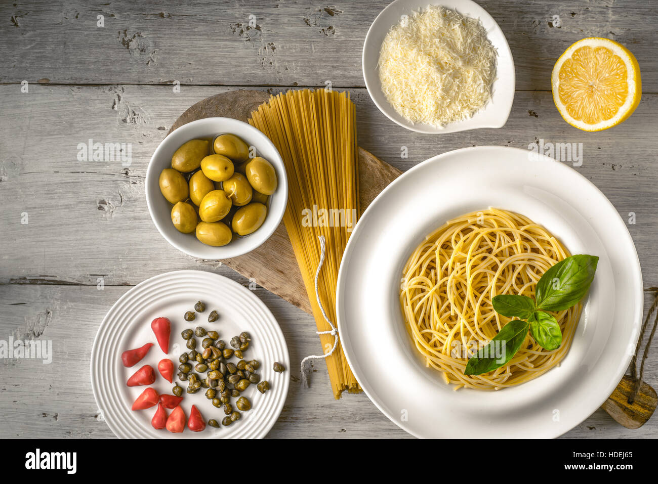 Raw and cooked spaghetti with different appetizer on the white wooden table top view. Concept of Italian cuisine - Stock Image