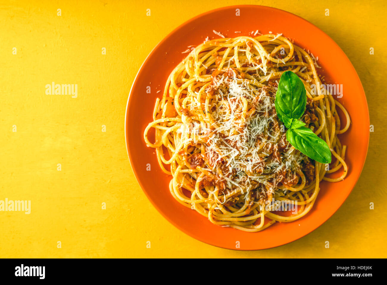 Spaghetti Bolognese on the orange plate on the yellow background top view - Stock Image