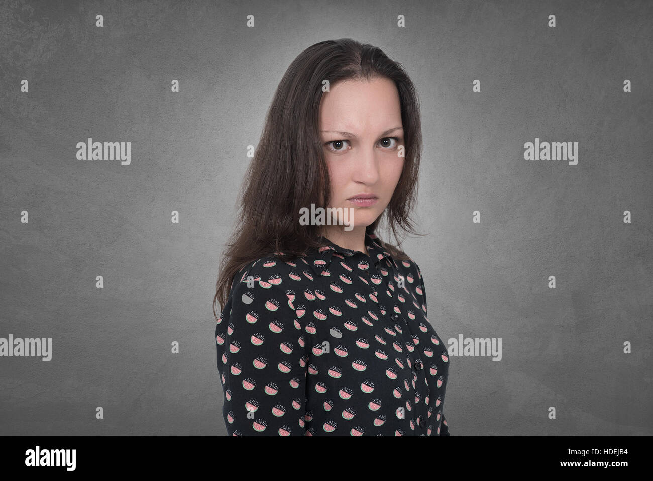 Angry Woman expression on grey wall - Stock Image