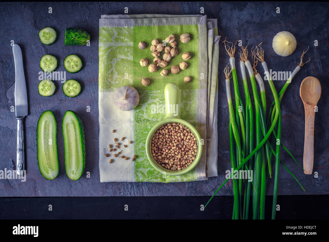 Green vegetables with seasoning on the dark stone background top view - Stock Image