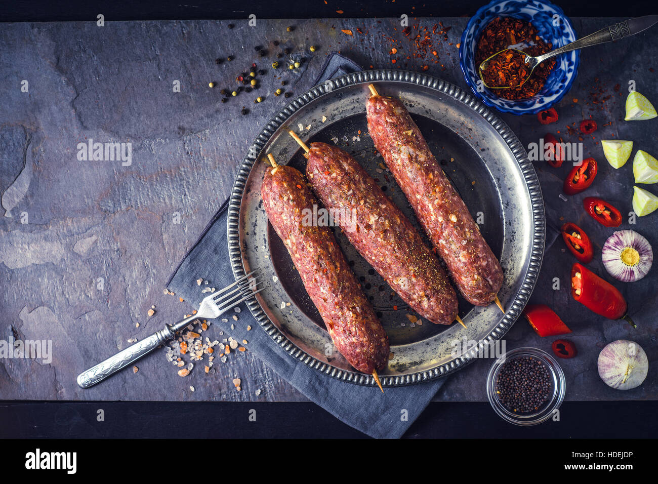 Raw kebabs with seasoning on the stone table top view - Stock Image
