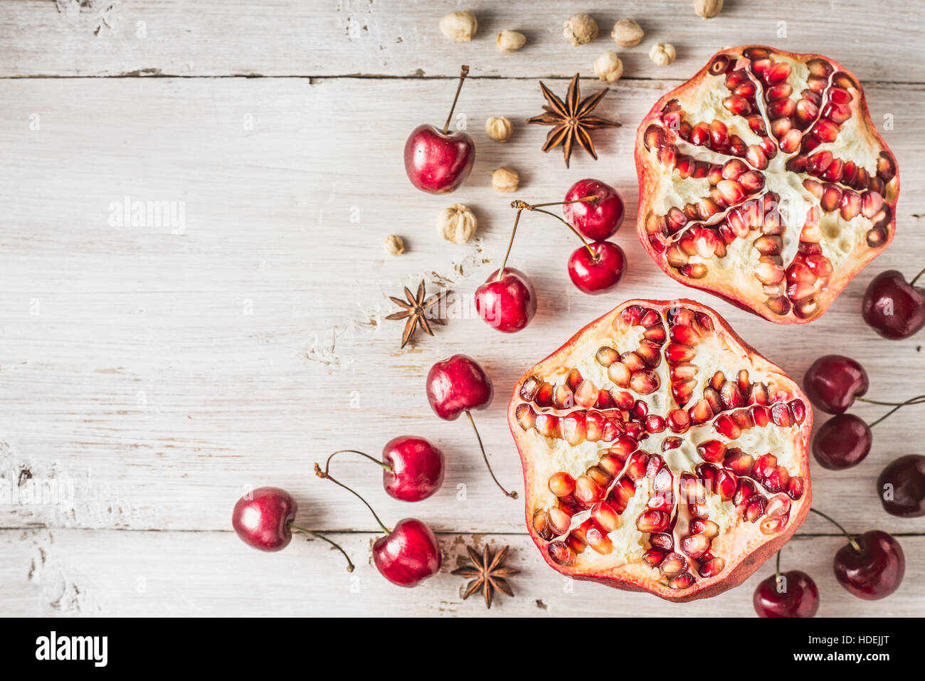 Still life with pomegranate , cherry and spices on the white wooden table. Concept of oriental fruits top view - Stock Image