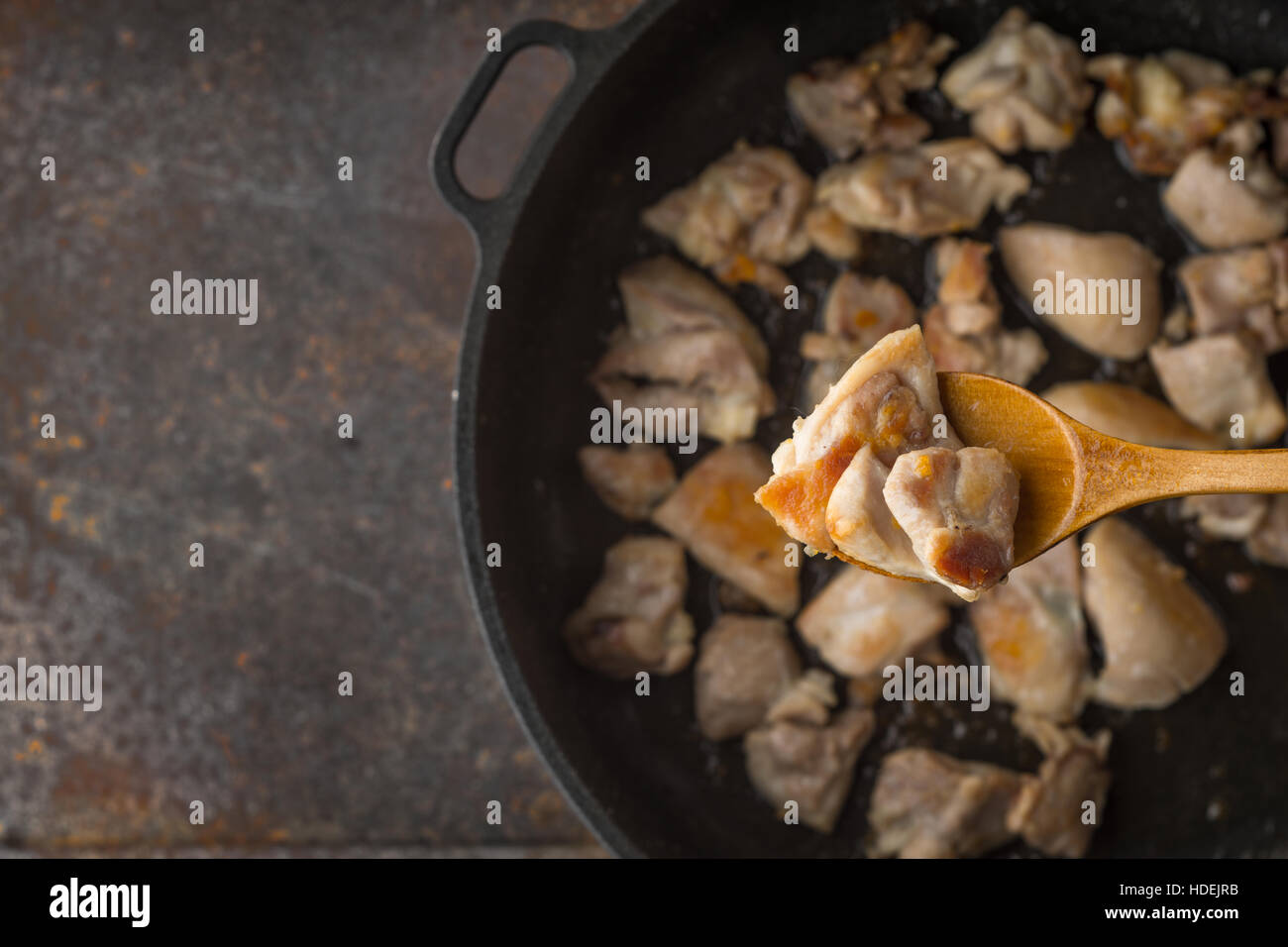 Fried chicken in the wooden spoon with blurred pan - Stock Image