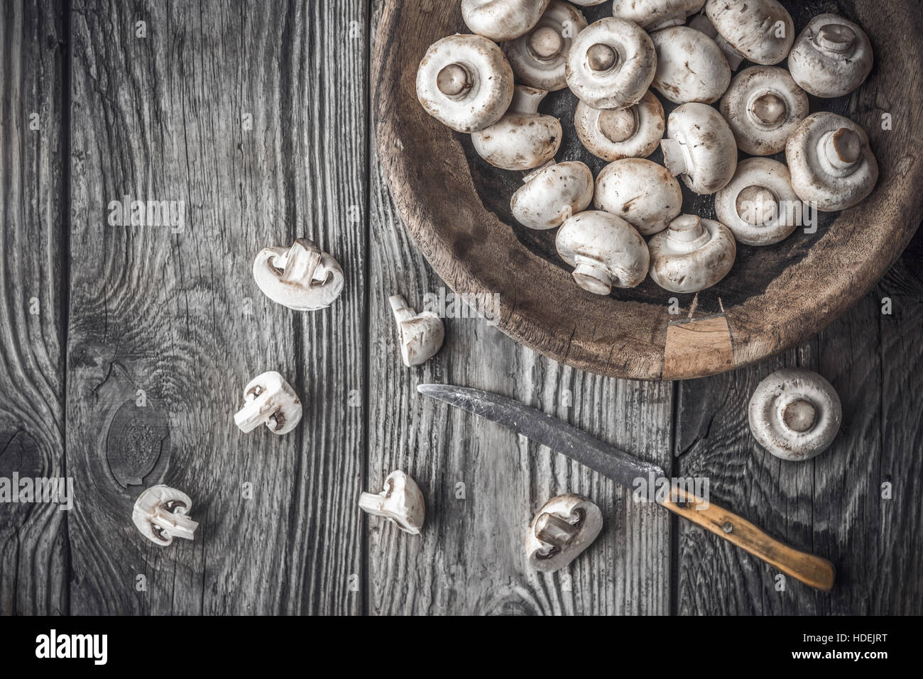 Champignon on the wooden bowl on the old table horizontal - Stock Image