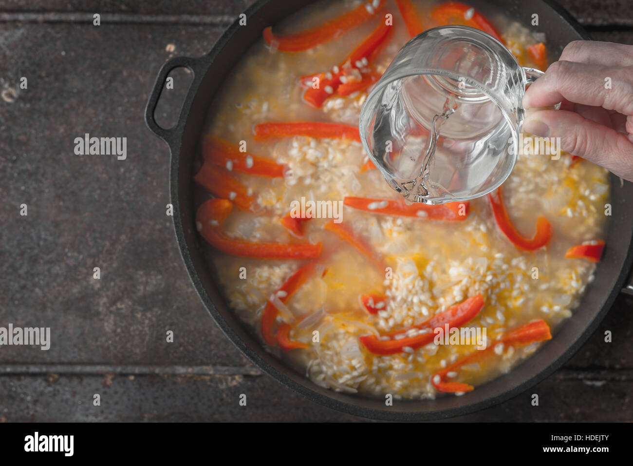 Adding water in the pan with rice and bell pepper top view - Stock Image