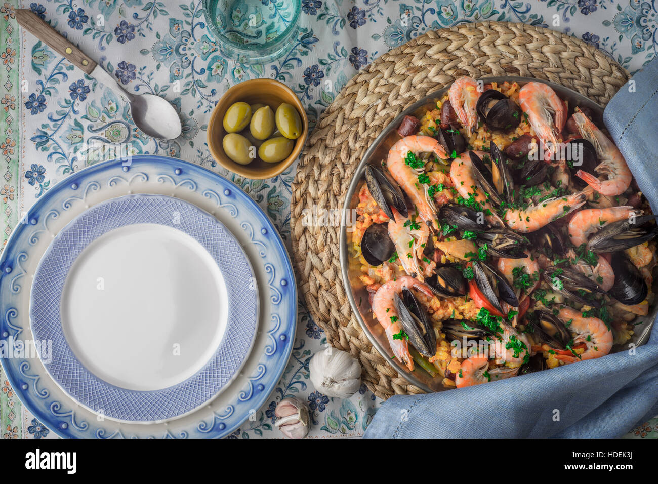 Paella on the metal plate on the beautiful napkin with tableware top view - Stock Image