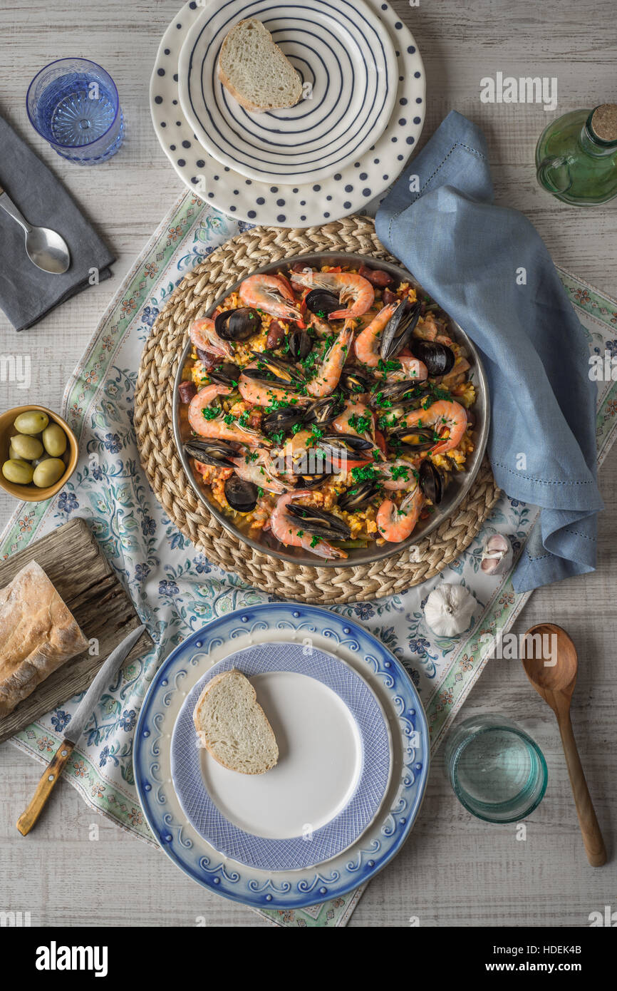 Paella on the metal plate on the beautiful napkin with tableware and bread vertical - Stock Image
