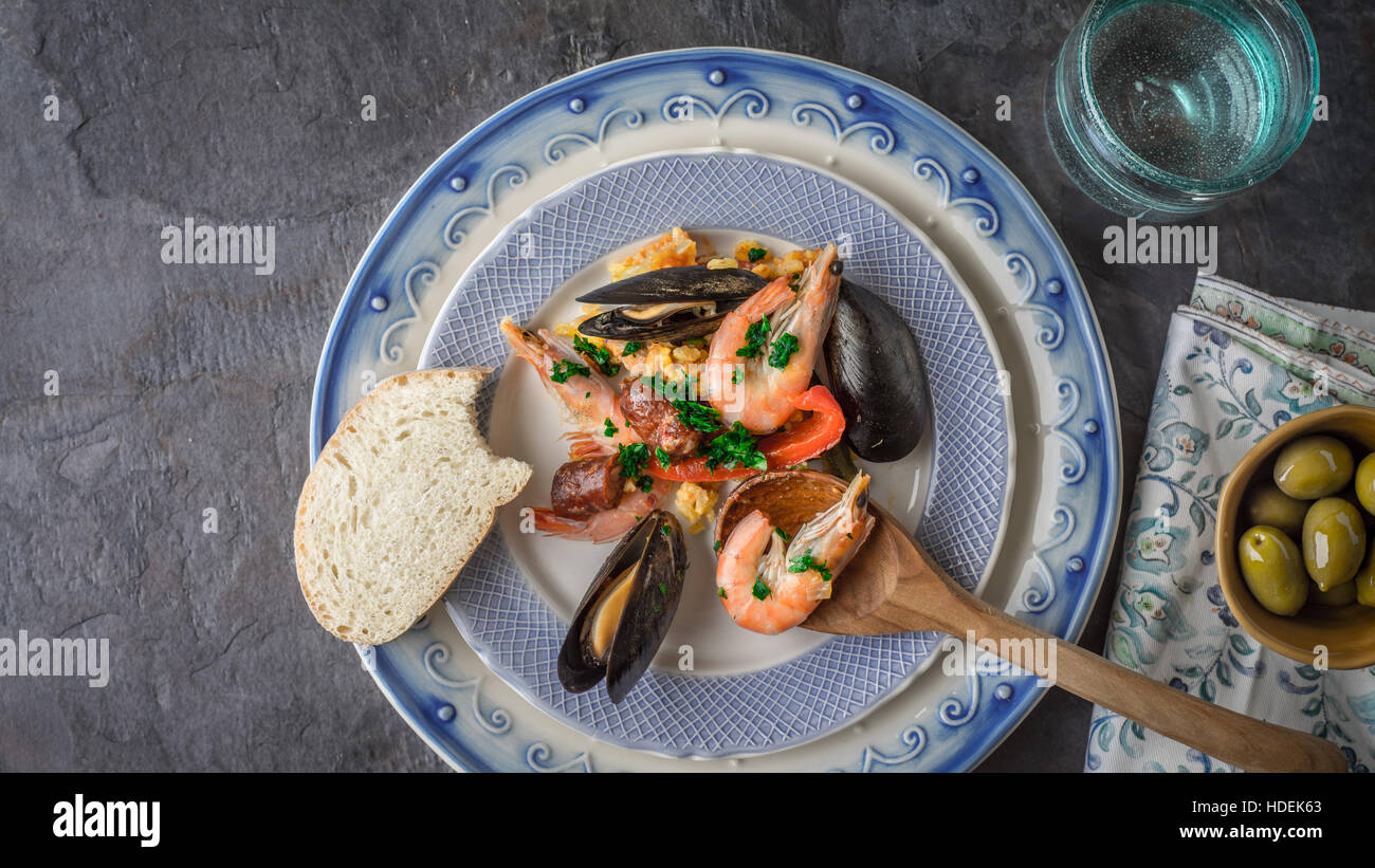Plate with paella on the dark stone table with different accessories top view - Stock Image