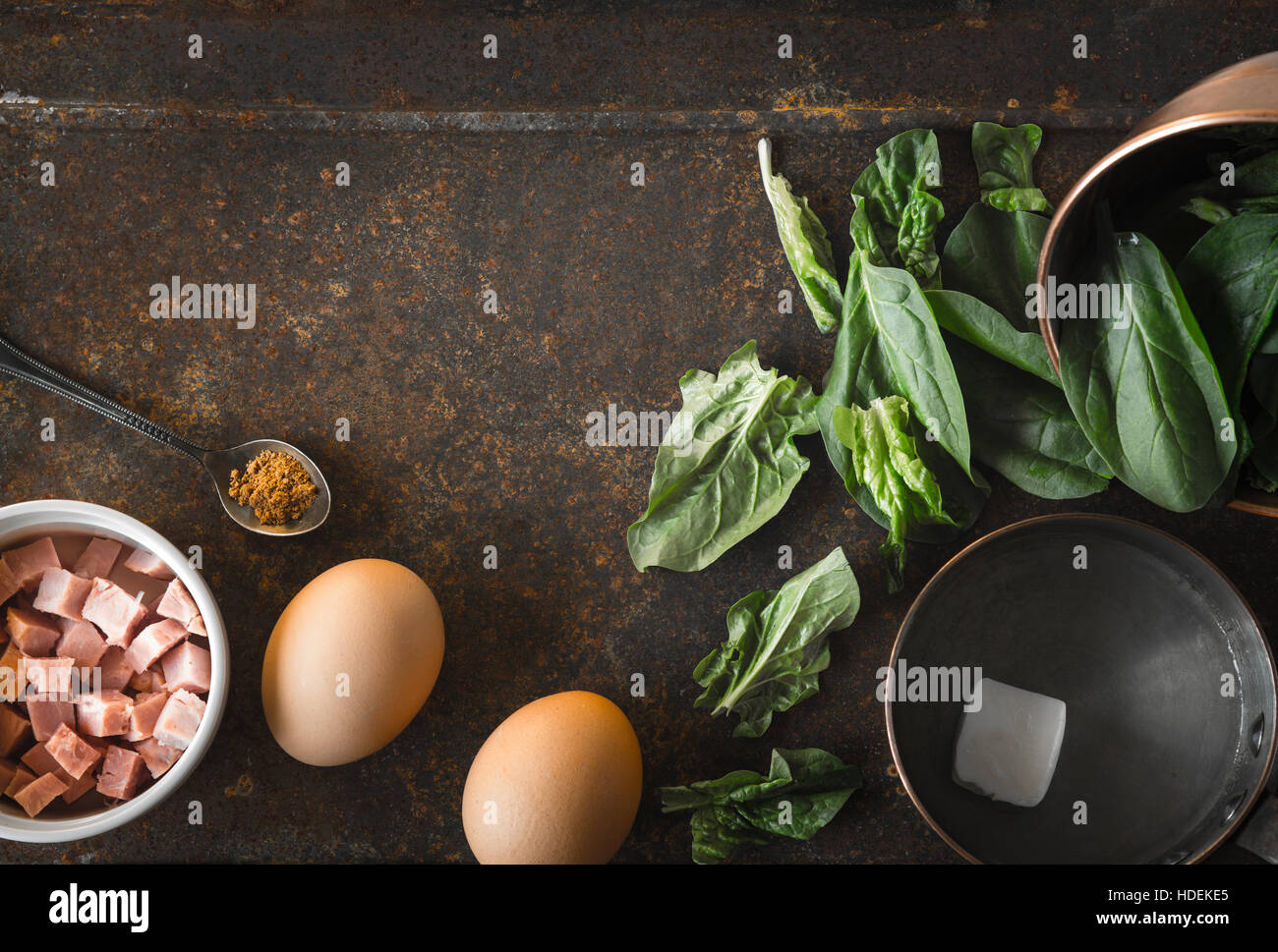 Ingredients for Florentine eggs with spinach on the rusty background top view - Stock Image