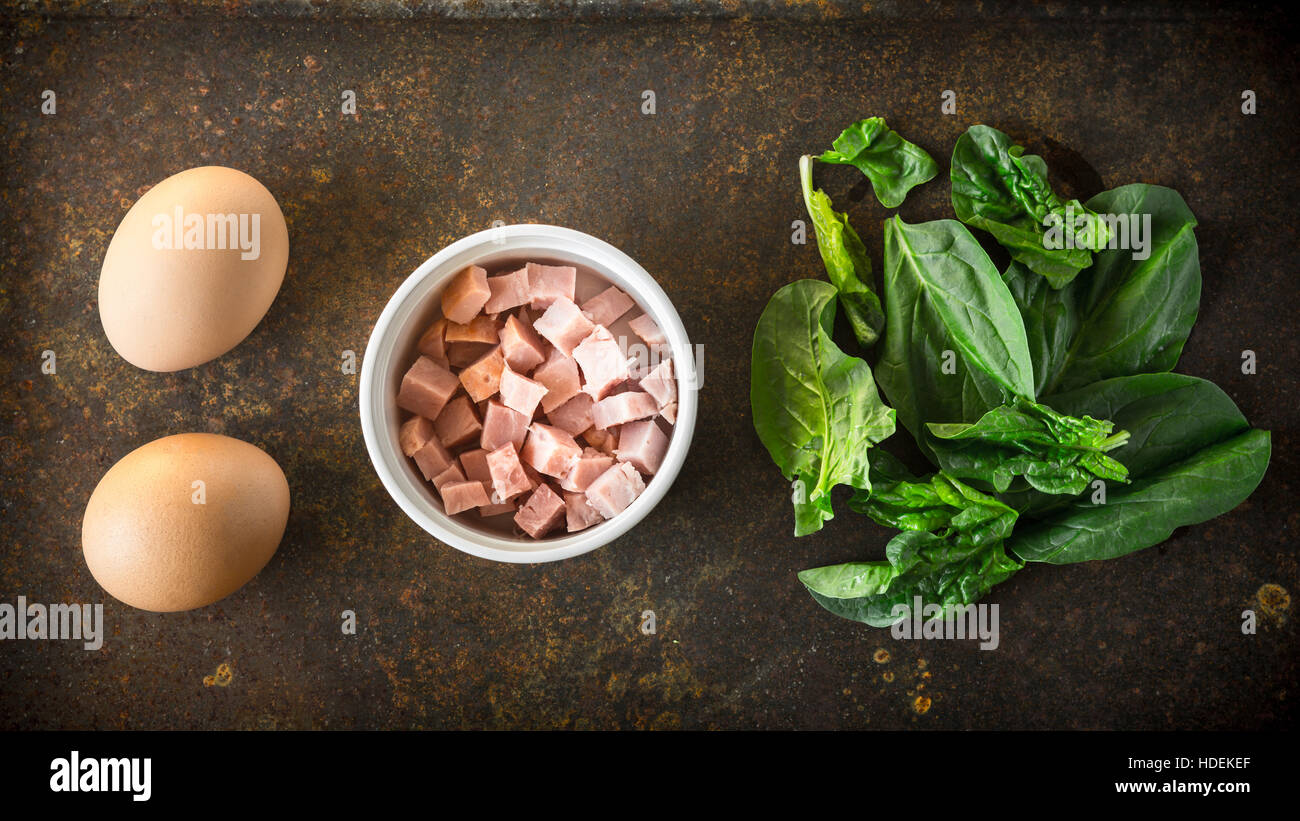Ingredients for Florentine eggs with spinach on the rusty background - Stock Image