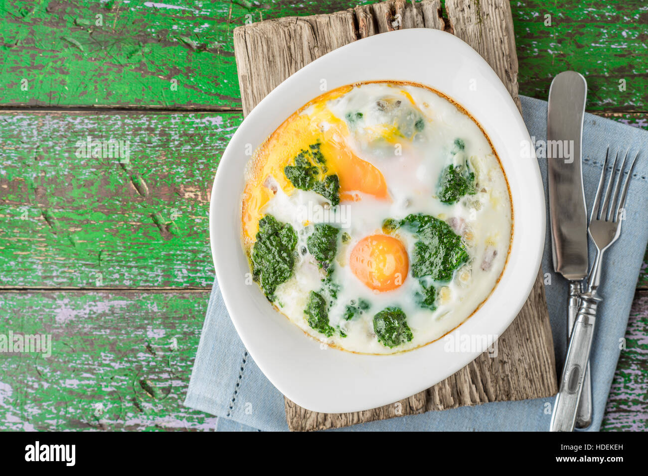 Florentine eggs with pureed spinach on the wooden table top view - Stock Image