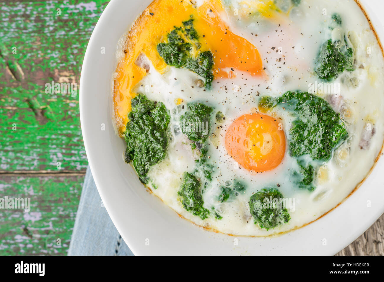 Florentine eggs with pureed spinach on the wooden table - Stock Image