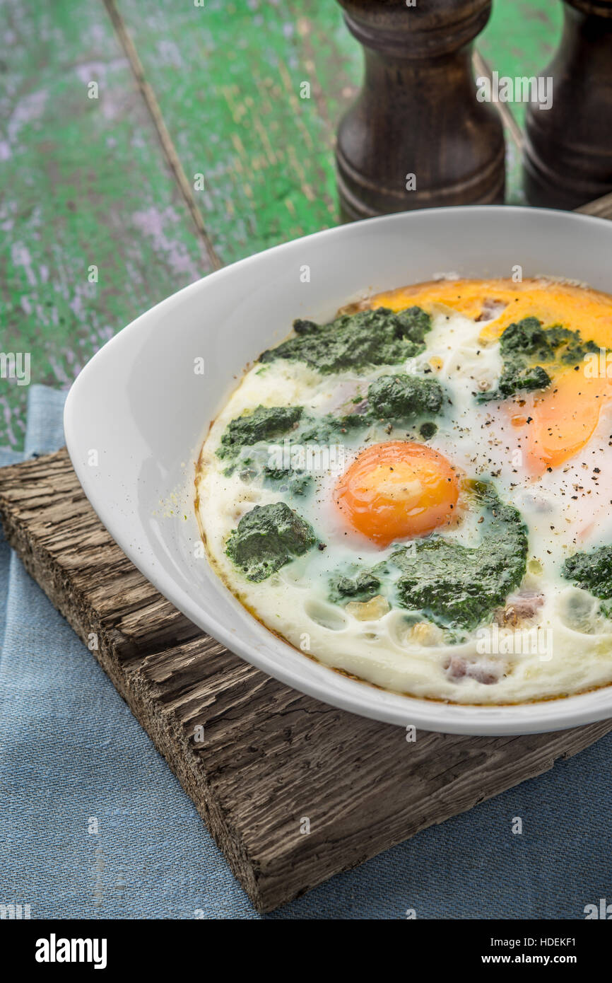 Florentine eggs with pureed spinach on the wooden table vertical - Stock Image