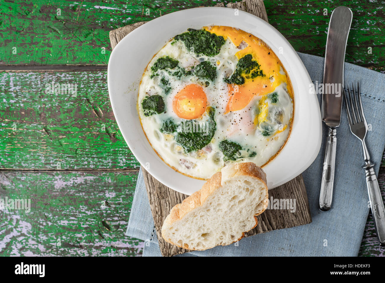 Florentine eggs with pureed spinach on the wooden table horizontal Stock Photo