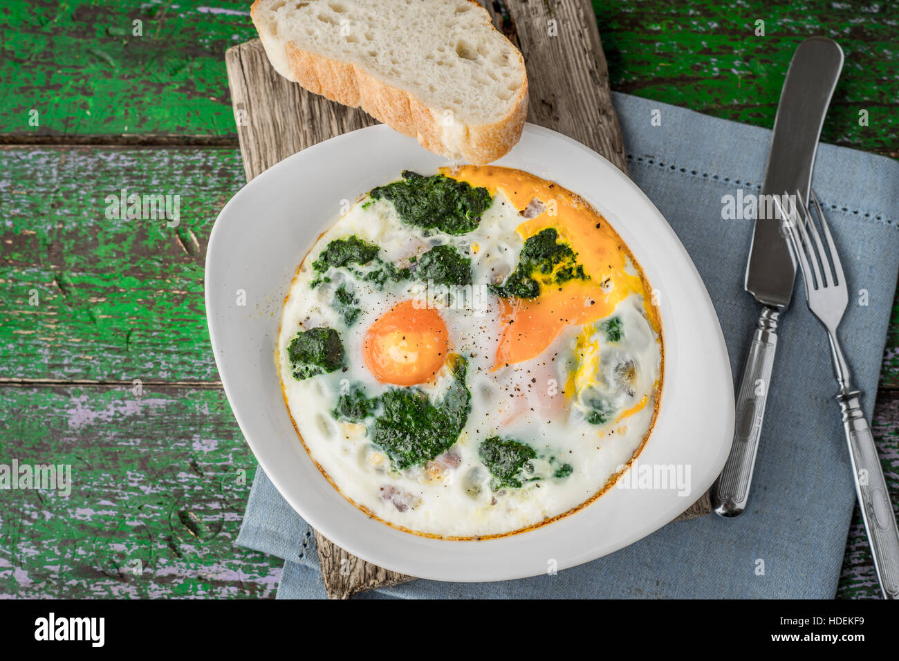 Florentine eggs with pureed spinach on the old wooden board - Stock Image