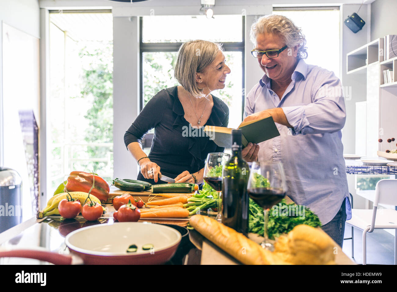 Senior couple cooking meal at home man reading a cooking recipe senior couple cooking meal at home man reading a cooking recipe book and woman cutting vegetables happy mature couple in the kitchen forumfinder Image collections