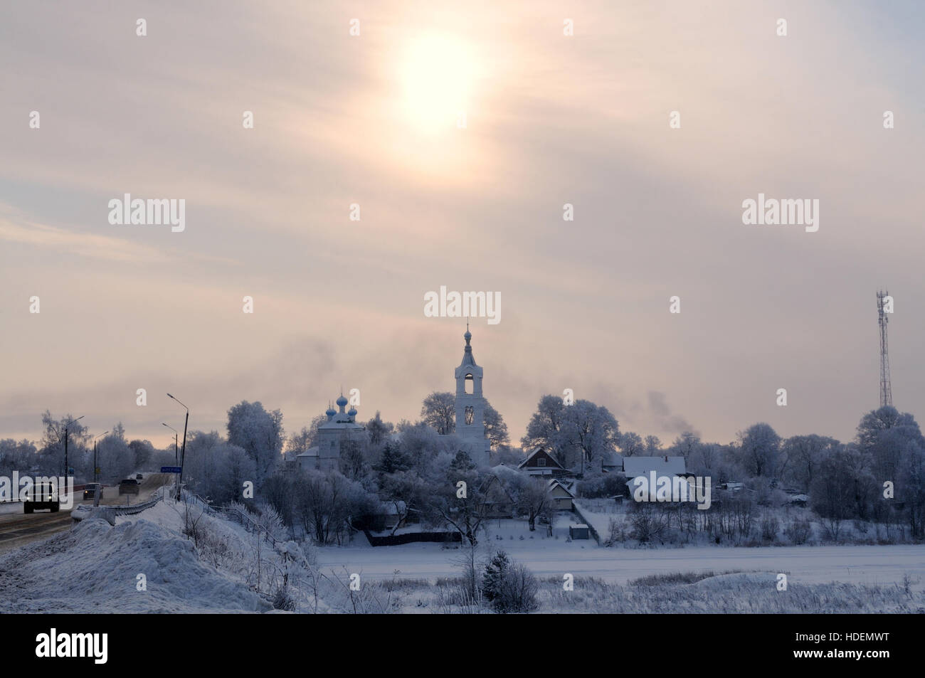 View on a village with church covered by snow on a frosty day over a small river, Porechye village, Nerl river, - Stock Image