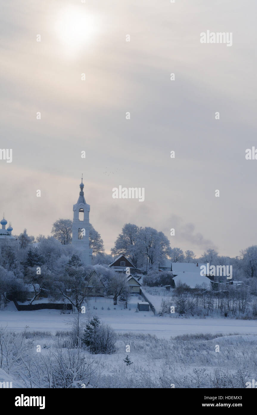 View on a village with church covered with snow on a frosty day over a small river, Porechye village, Nerl river, - Stock Image