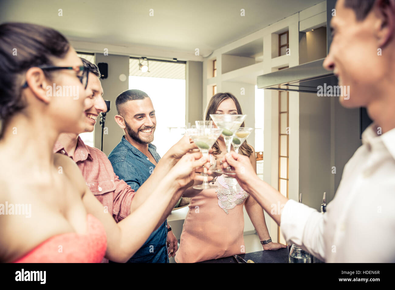 Group of friends having party at home and toasting cocktail glasses - Stock Image