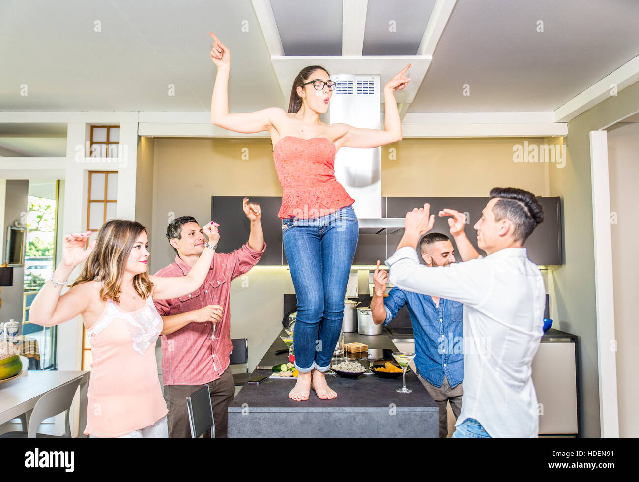 Group of friends partying at home, dancing and drinking cocktails - Stock Image