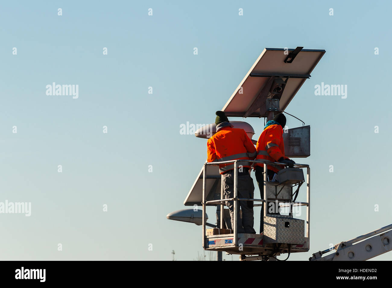 Workers in lift bucket during the maintenance of streetlight powered by a solar panel. - Stock Image