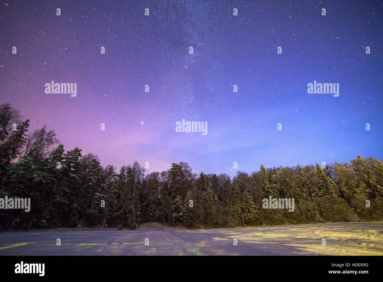 A clear night showing stars. Forest and frozen lake in Estonia. - Stock Image
