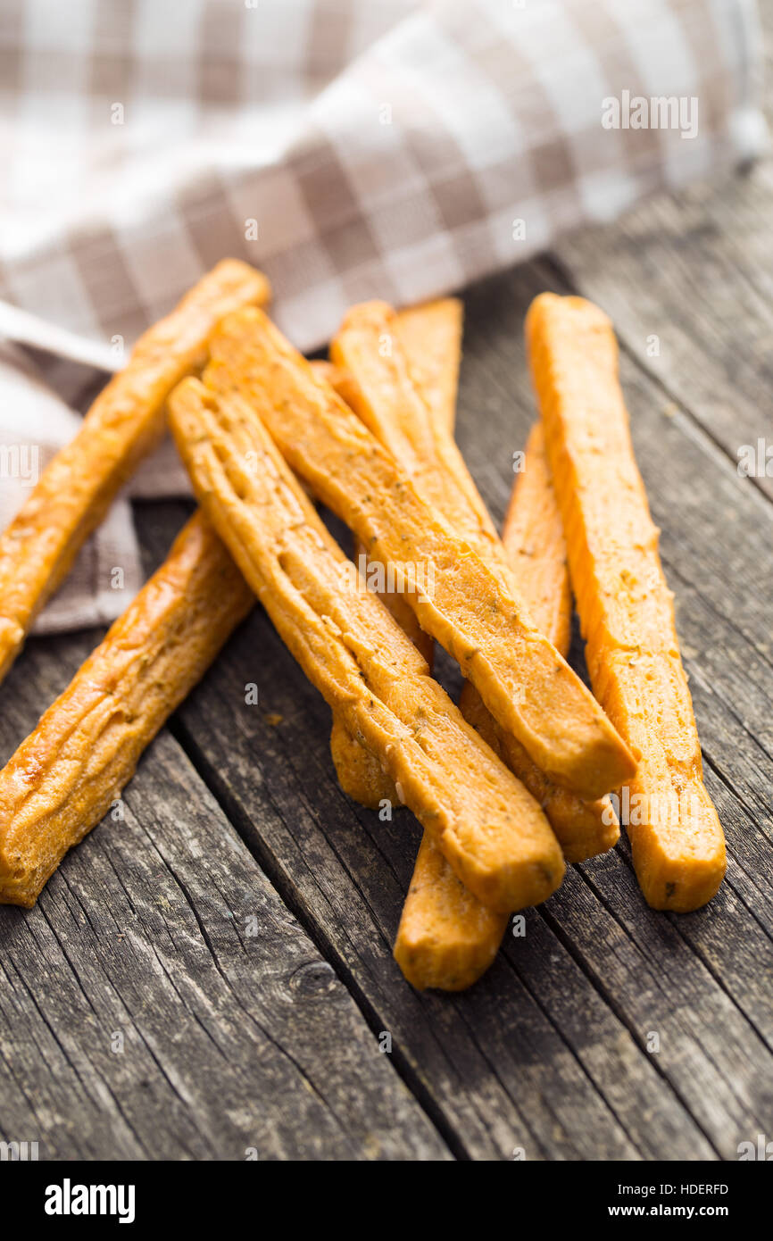 Crispy bread sticks on old wooden table. - Stock Image