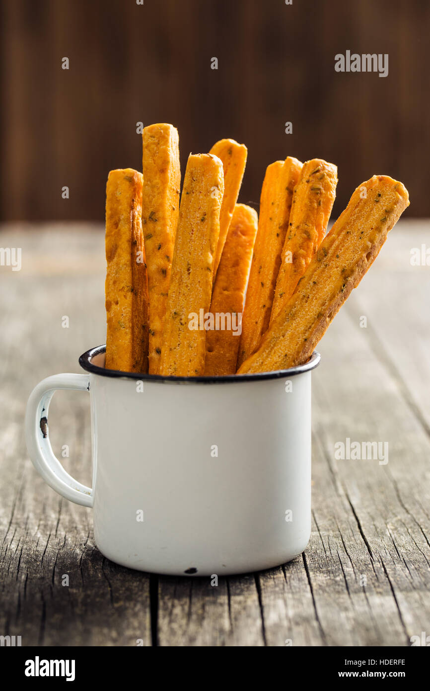 Crispy bread sticks in old cup. - Stock Image