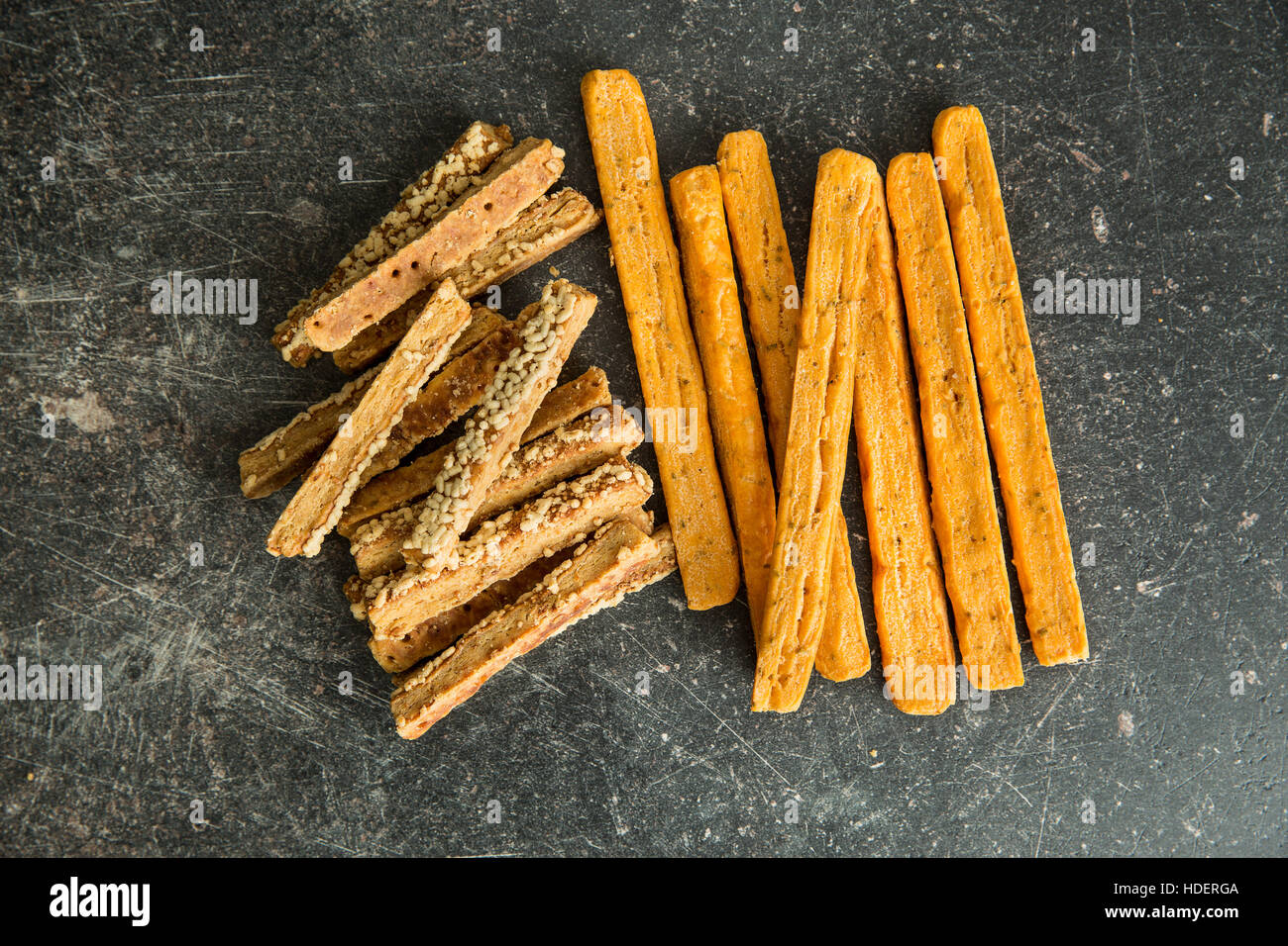 Crispy bread sticks with cheese on old kitchen table. - Stock Image