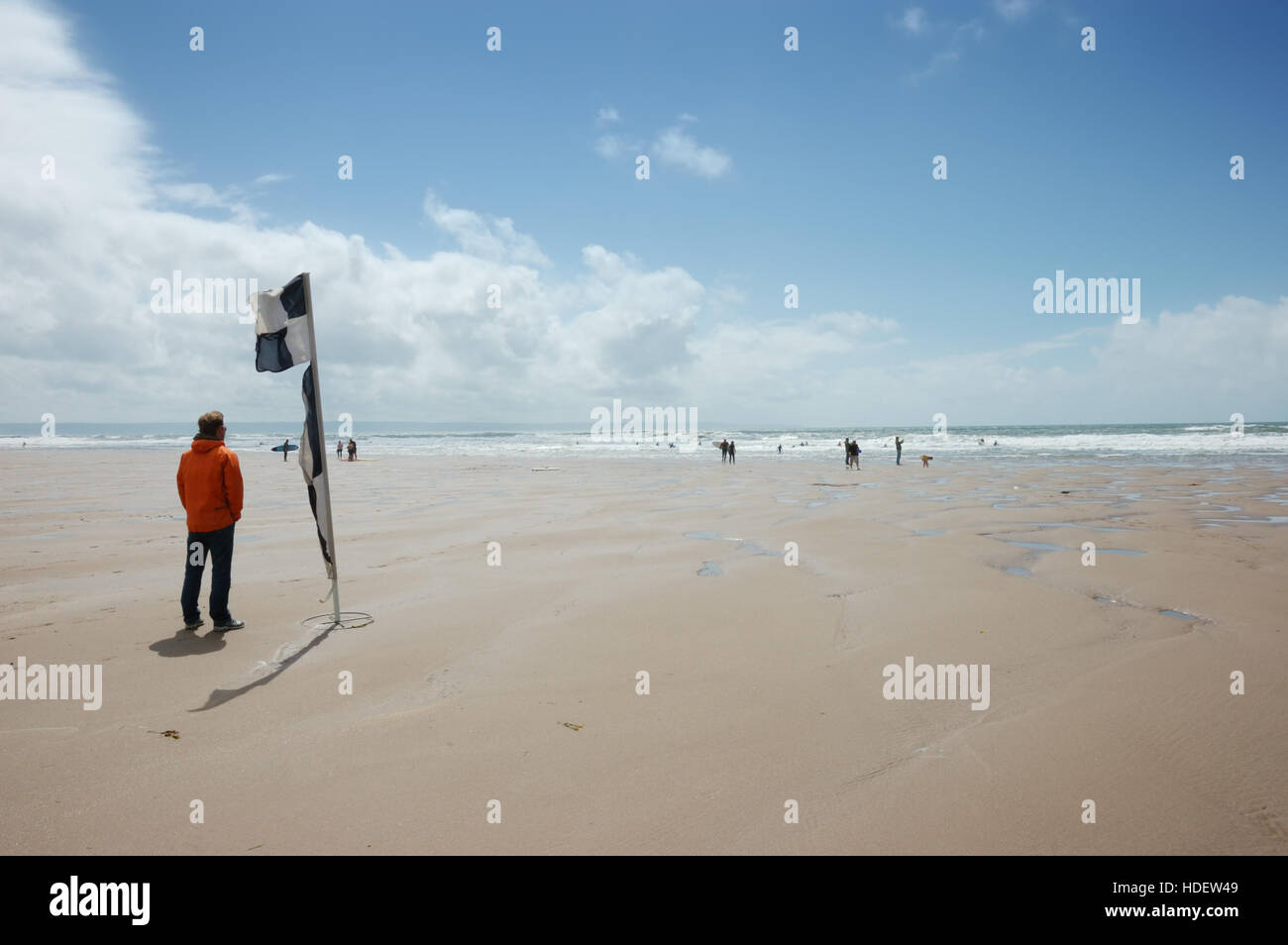 A male lifeguard standing by a black and white chequered RNLI beach safety flag keeping a lookout on Croyde Bay Stock Photo