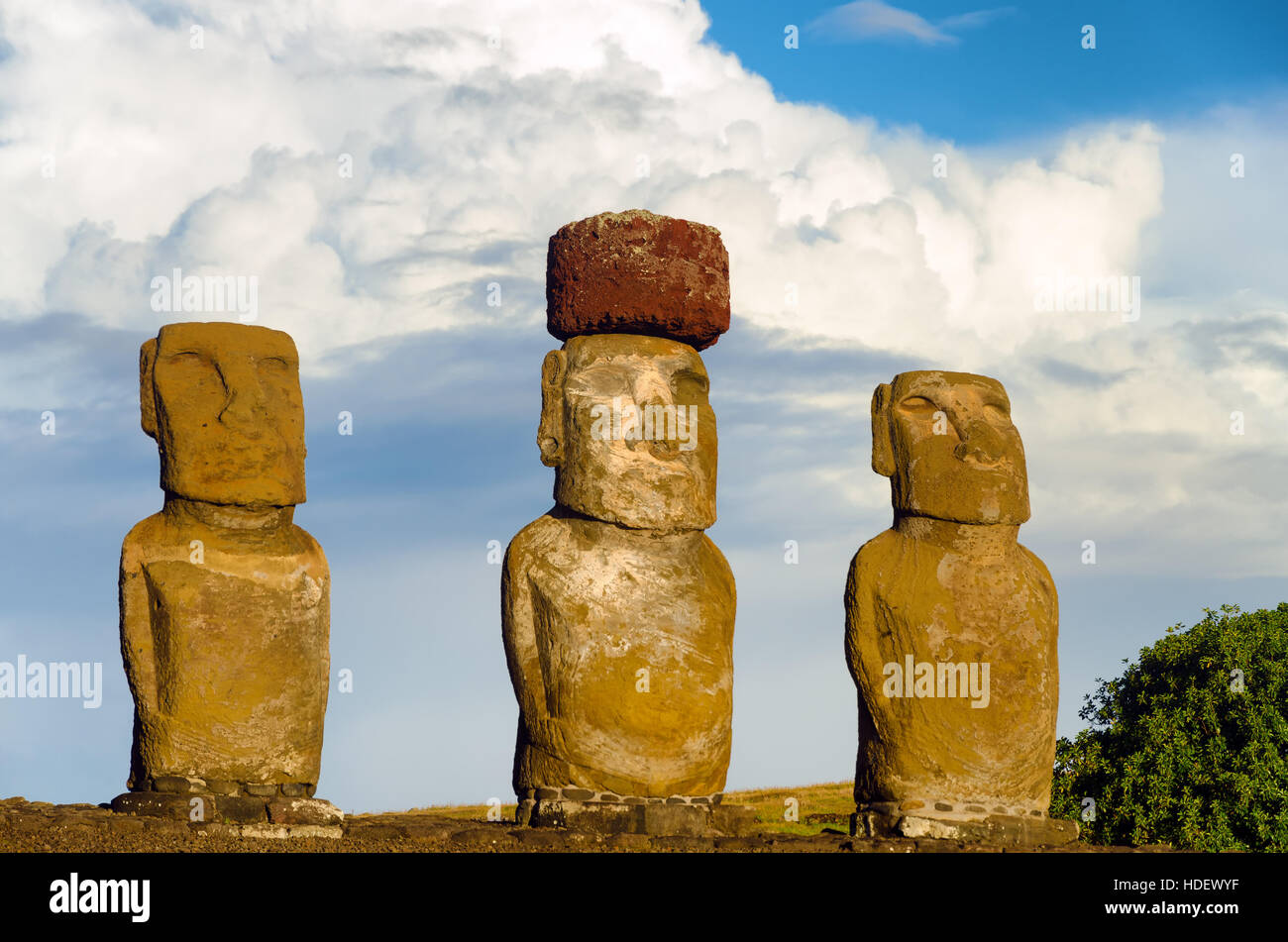 View of three Moai with dramatic clouds on Easter Island in Chile - Stock Image